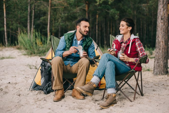 Couple Sitting in Chairs on a Camping Trip