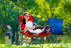 Happy Woman Sitting In a Camping Chair