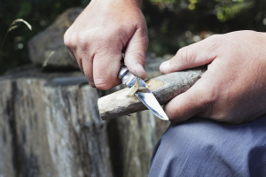 Man Shaving Wooden Branch with a Small Pocket Knife