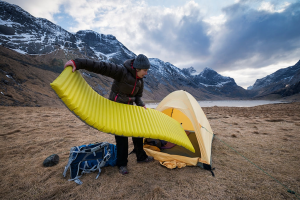 Man Setting Up a Camping Mattress