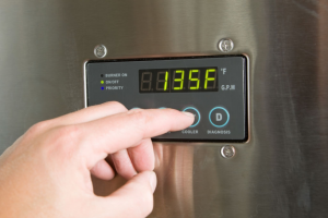 Man Adjusting the Temperature on a Tankless Water Heater