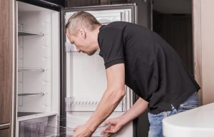 Man Adjusting RV Refrigerator Shelves