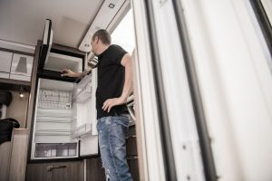 Man Opening Compressor Fridge in RV