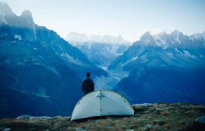 Backpacker on a Mountain Beside his One-Person Tent