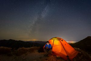 Man Camping Under Stars Next to Small Tent