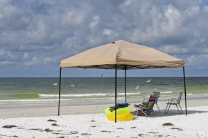 Canopy tent on the beach providing shade to beach chairs