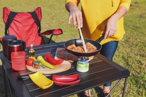 Woman cooking food on a camping table