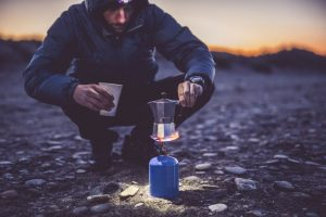Man with a coffee kettle on a camp stove