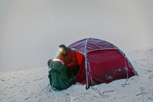 Man Camping in Snow with rolled up sleeping bag